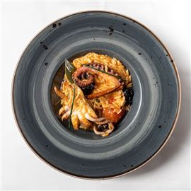 Orzo pasta 'yiouvetsi' casserole with octopus, cuttlefish and plum